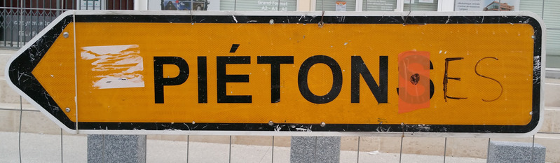 photographie d'un graffiti inclusif: «piétons» devient «piéton·es»